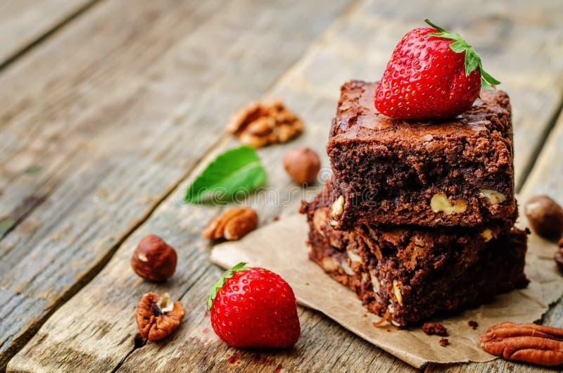 De browniecake van de chocoladenoot met aardbeien wordt verfraaid die royalty-vrije stock afbeelding