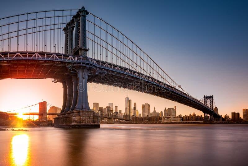 De Brug die van Manhattan de horizon van New York ontwerpen bij zonsondergang stock foto