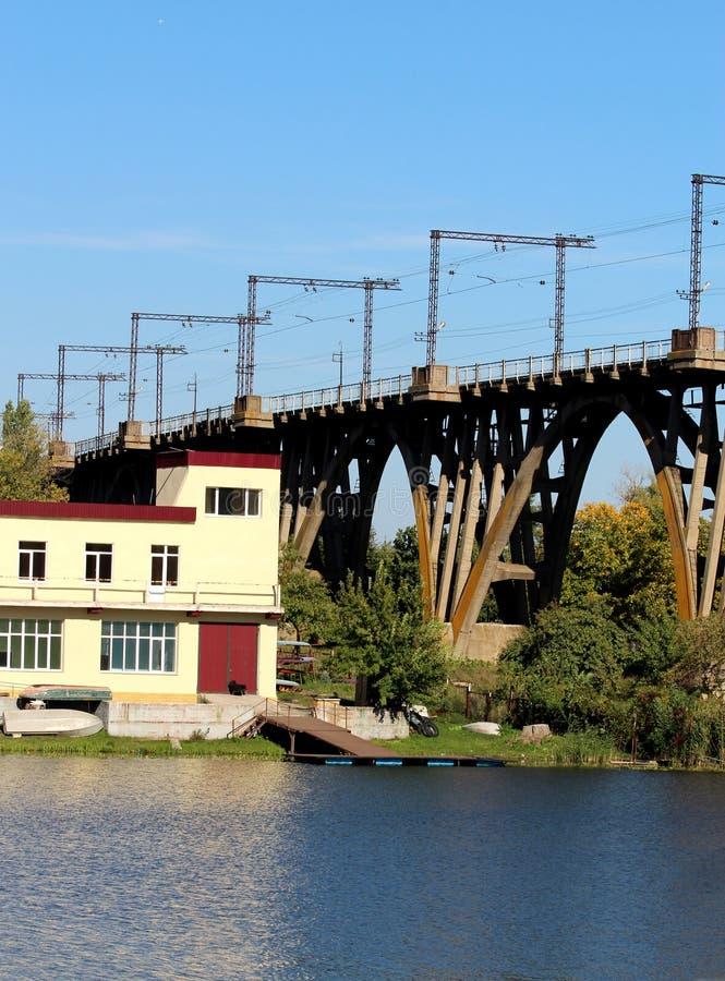 De brug die zich in het water bevindt De brug waarover de goederentreinen zich bewegen Dichtbij is de rivier en het gebouw stock afbeeldingen