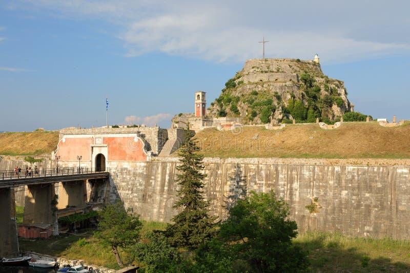 De Brug, de poort, de Klokketoren en het Kasteel dichtbij de Landpiek met de Vuurtoren van de Oude Vesting van Korfu, Kerkyra, Co stock foto's