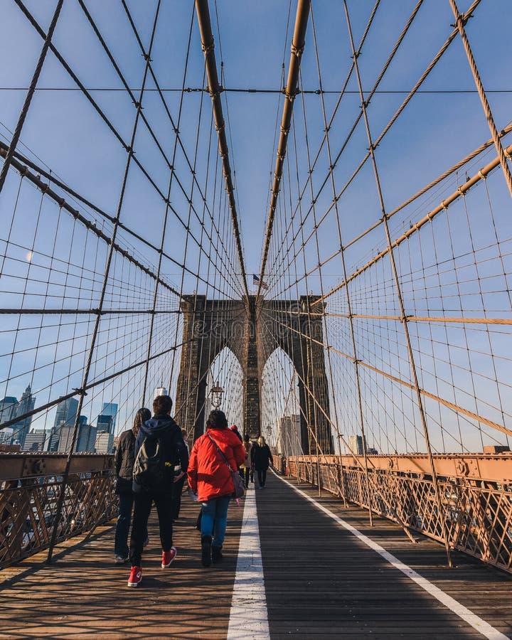 De Brug van Brooklyn bij zonsondergang met mensen die overdwars lopen stock foto's