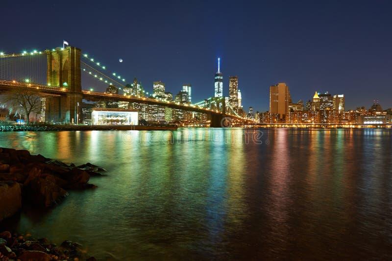 De Brug van Brooklyn met de lagere horizon van Manhattan bij nacht stock afbeelding