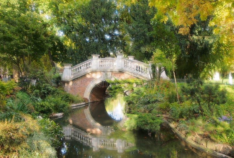 De brug van de steenboog over een vijver in Parc Monceau in Parijs, Frankrijk royalty-vrije stock fotografie
