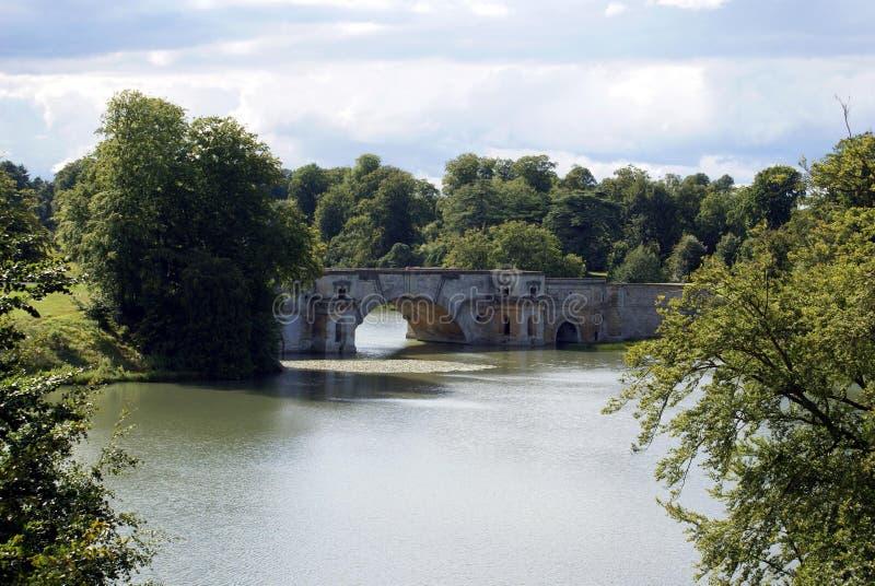 De Brug van het Blenheimpaleis over een meer in Engeland stock afbeeldingen