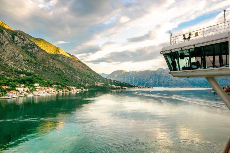 De brug van het cruiseschip in Montenegro Kotor Baai die toneeldorp met lange bergen tijdens zonsopgang bekijken stock foto