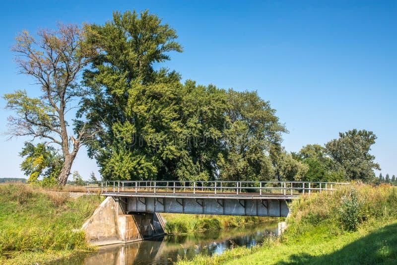 De brug van het de spoorwegstaal van het plattelandslandschap over waterkanaal stock foto