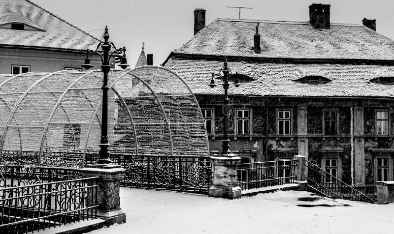 De brug van ligt in sibiu en oude historische die gebouwen in sneeuw in Sibiu, Roemenië wordt behandeld royalty-vrije stock fotografie