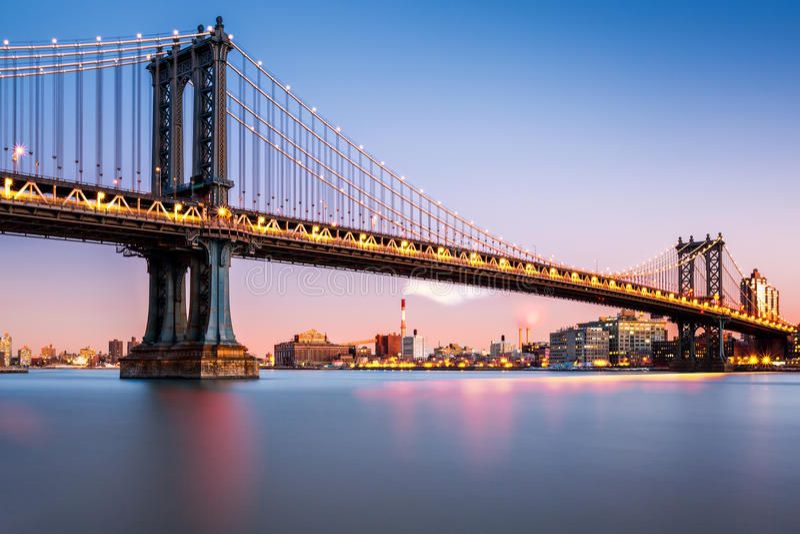 De Brug van Manhattan bij schemer wordt verlicht die royalty-vrije stock afbeeldingen