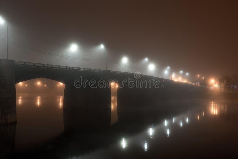 De brug van de stadsweg over rivier in dichte die mist bij nacht door lantaarns wordt verlicht royalty-vrije stock afbeeldingen