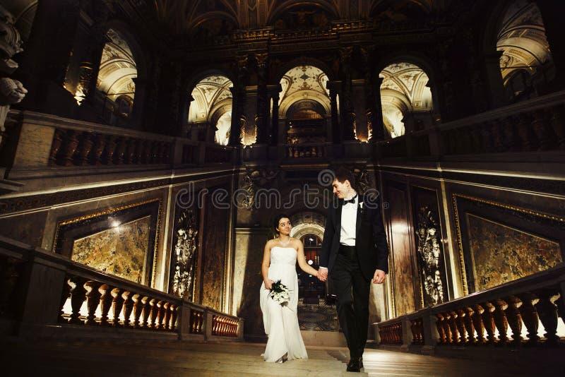De bruid bekijkt een bruidegom die boven in een oude zaal van Wenen t gaan stock afbeelding