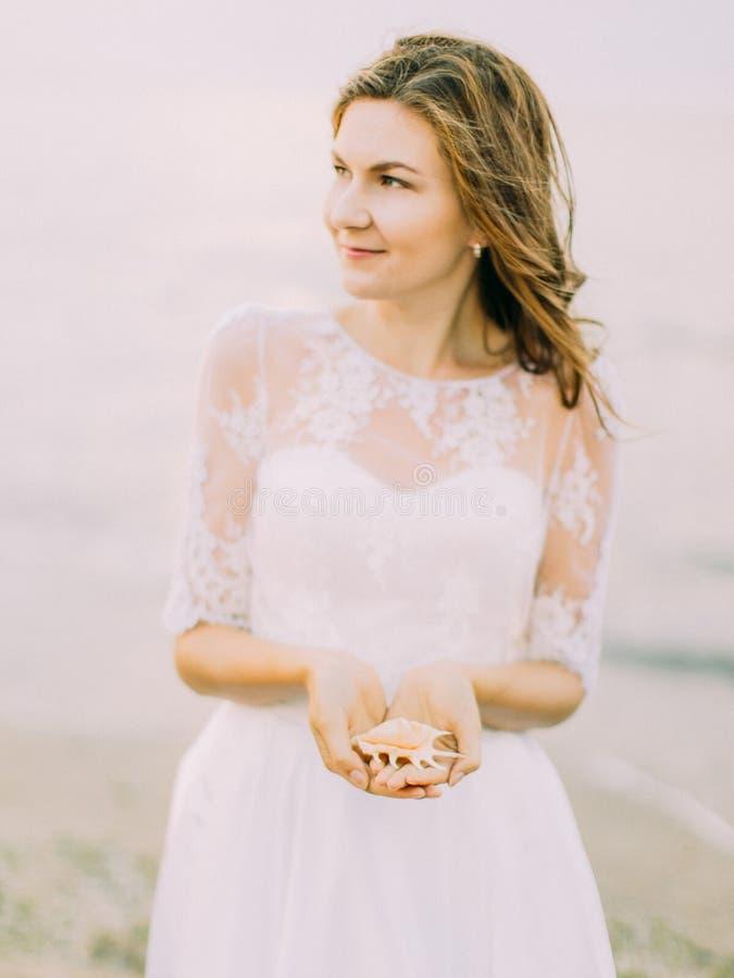 De bruid bekijkt de rechterkant terwijl het houden van shell bij de achtergrond van het overzees stock afbeelding