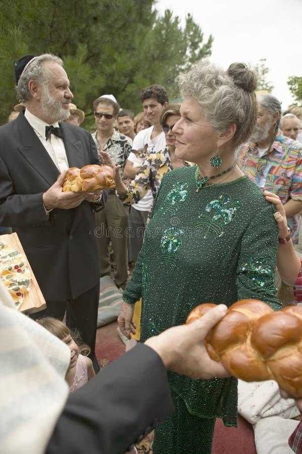 De bruid, de bruidegom en de gasten breken brood bij een traditioneel Joods huwelijk in Ojai, CA stock afbeelding