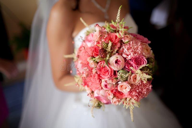 De bruid die een boeket van roze houden stock foto's