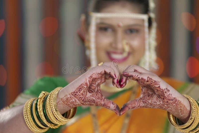 De bruid die hartvorm tonen met dient Indisch Hindoes huwelijk in royalty-vrije stock foto's