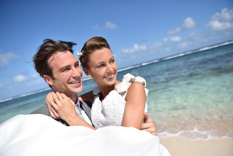 De bruid die van de bruidegomholding op het strand glimlachen royalty-vrije stock fotografie