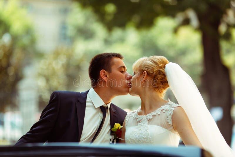 De bruid die van Fiancekussen teder in een oude auto zitten stock foto