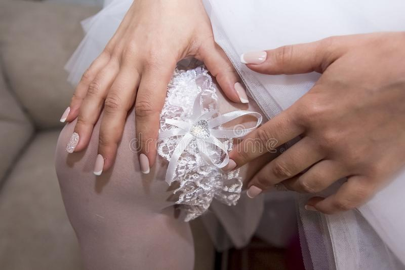 De bruid draagt een kant witte kouseband op haar been stock foto's