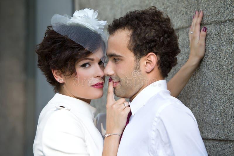 De bruid drukt passionately bruidegom tegen muur royalty-vrije stock foto
