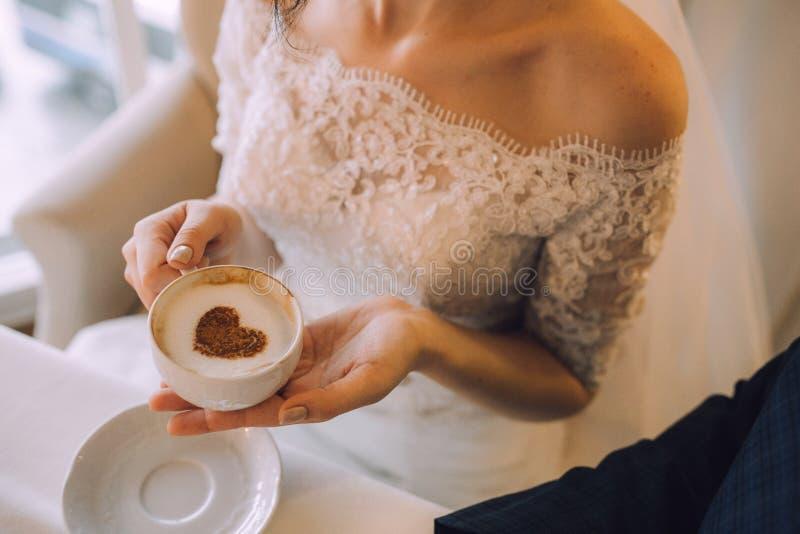 De bruid in een elegante kleding van het kanthuwelijk houdt een kop met cappuccino, waarop een kaneel een hart wordt getrokken royalty-vrije stock fotografie