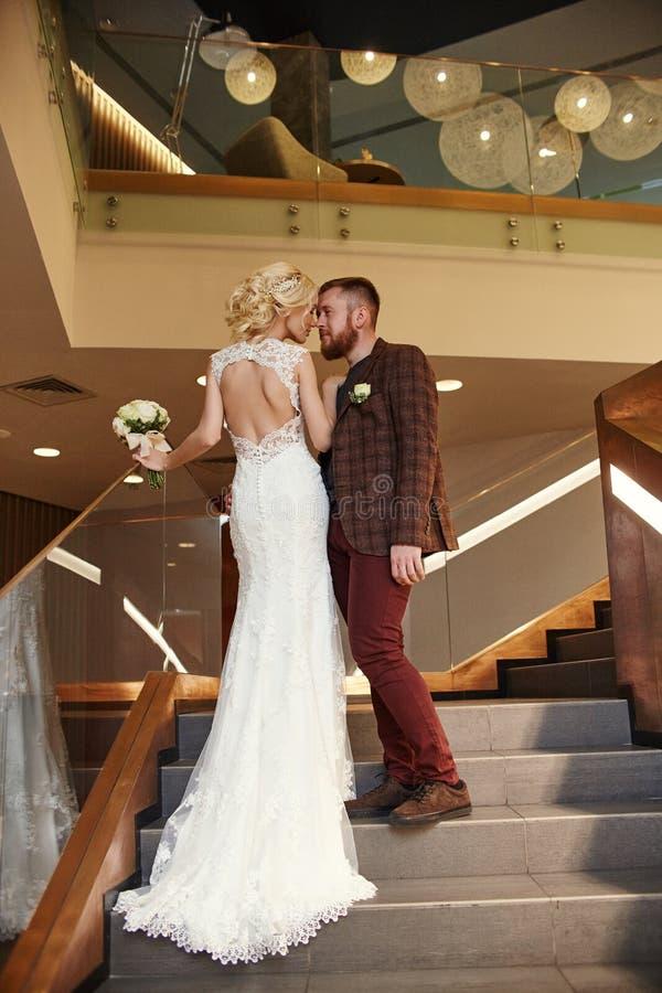 De bruid in een elegante lange kleding met een trein en de bruidegom bevinden zich op grote treden, paar in liefdeomhelzingen op  royalty-vrije stock foto's