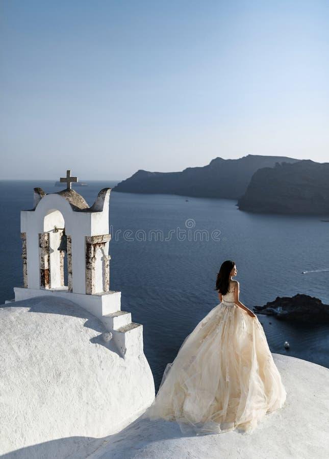 De bruid in een mooi huwelijksplan bevindt zich op het dak van het huis en geniet van de mening van het overzees en de hemel bij  stock foto's