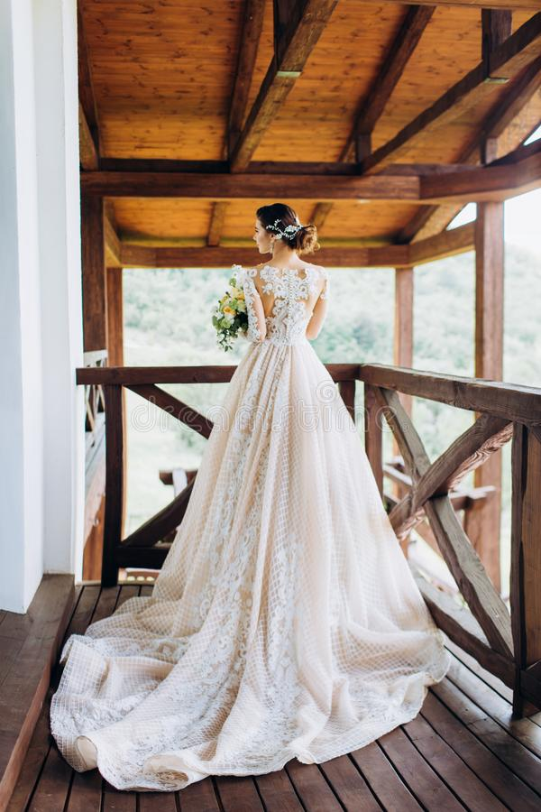 De bruid in een prachtige, witte, huwelijkskleding met een lange trein stock fotografie