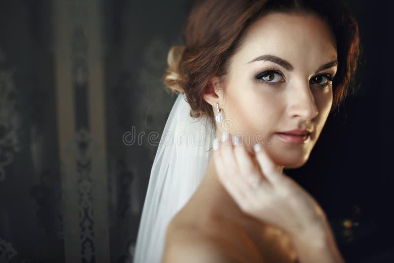 De bruid in een sluier raakt haar gezicht met hand stock foto's