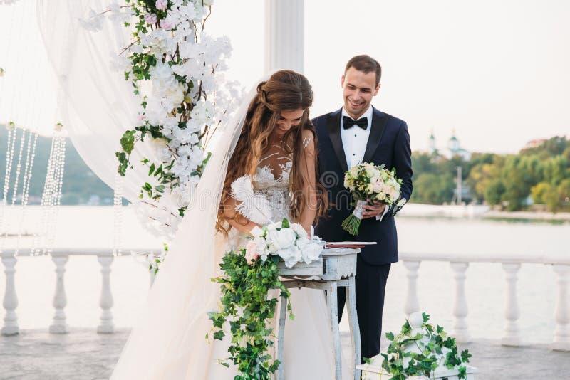 De bruid in een witte kleding bij huwelijksdag zet een handtekening dichtbij de boog met een meer op achtergrond Jonggehuwdentrib stock fotografie