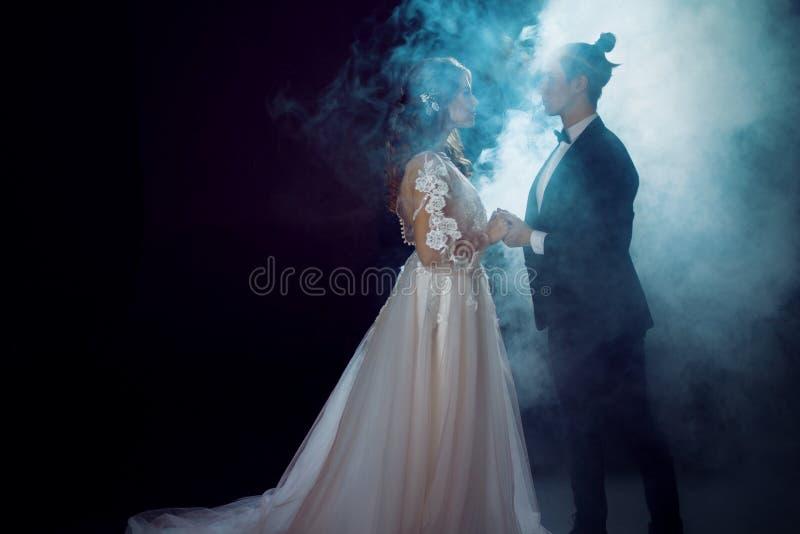 De bruid en de bruidegom bekijken elkaar Romantisch geheimzinnig portret op donkere achtergrond in rook Man en vrouw, huwelijkskl royalty-vrije stock foto