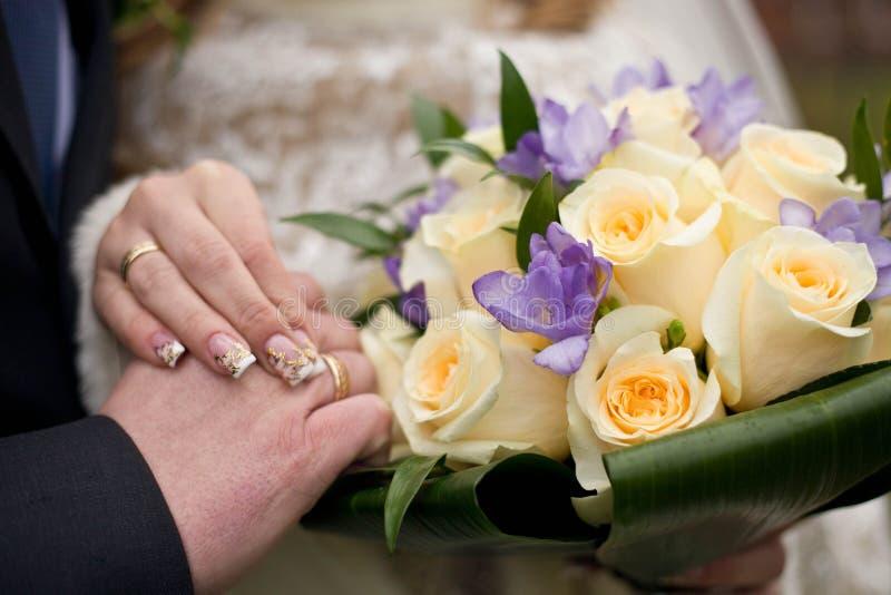 De bruid en de bruidegom bij het huwelijk, die handen houden stock fotografie
