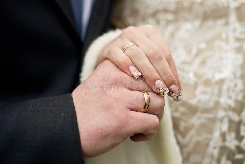 De bruid en de bruidegom bij het huwelijk, die handen houden stock afbeelding