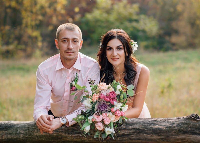 De bruid en de bruidegom dichtbij de houten omheining Portret van een jong paarclose-up De mensen lachen Het meisje heeft a stock foto's