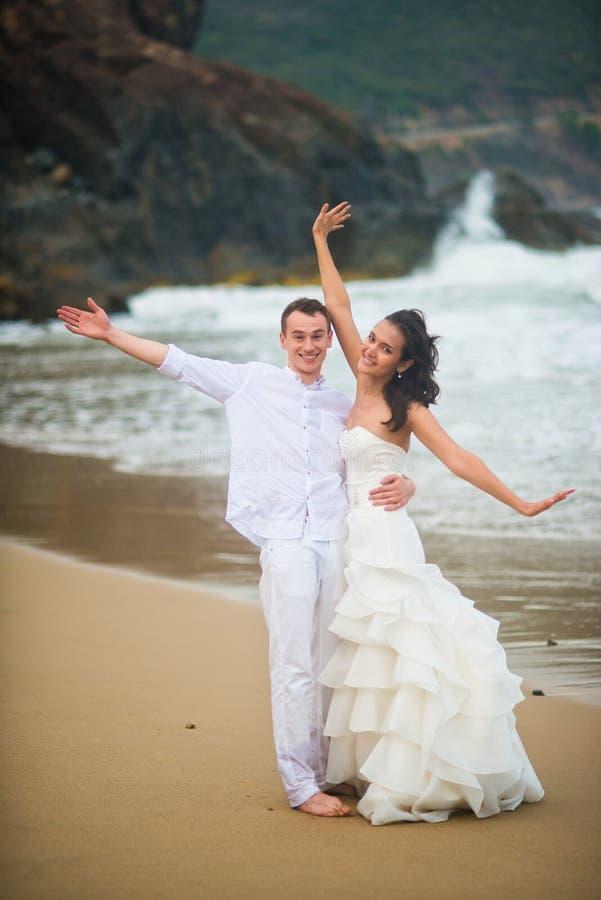 De bruid en de bruidegom hebben pret door het overzees paar in liefde op een verlaten strand royalty-vrije stock afbeelding