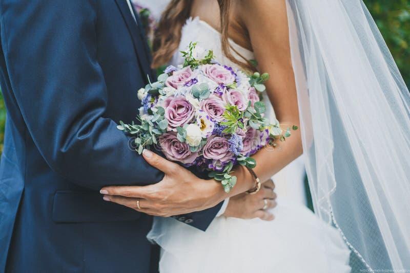 De bruid en de bruidegom houden een huwelijksboeket royalty-vrije stock afbeeldingen