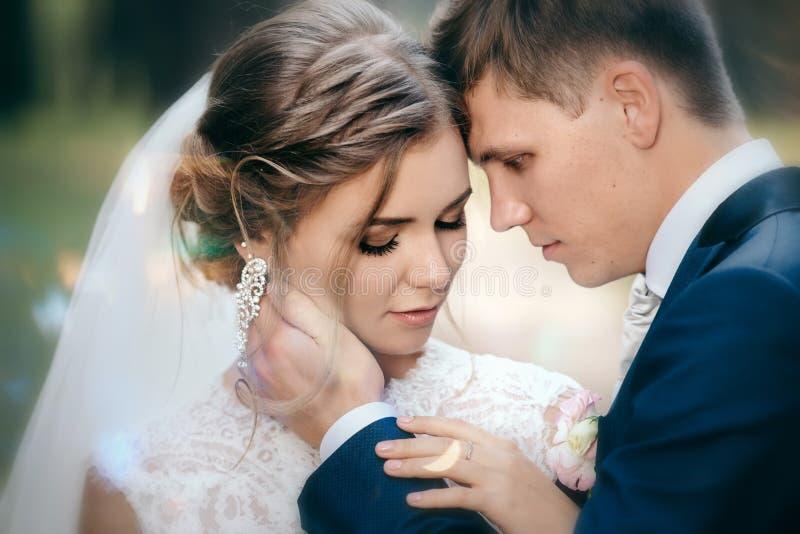 De bruid en de bruidegom in huwelijk kleden zich op natuurlijke achtergrond Het overweldigende jonge paar is ongelooflijk gelukki stock foto