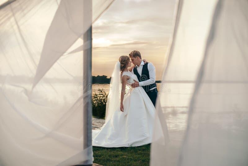 De bruid en de bruidegom in huwelijk kleden zich op natuurlijke achtergrond Ne stock foto