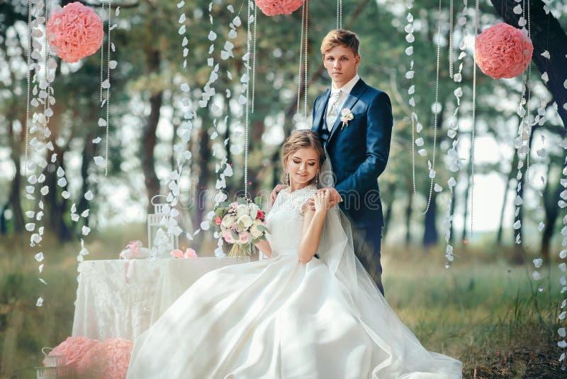 De bruid en de bruidegom in huwelijk kleden zich op natuurlijke achtergrond Wij royalty-vrije stock foto
