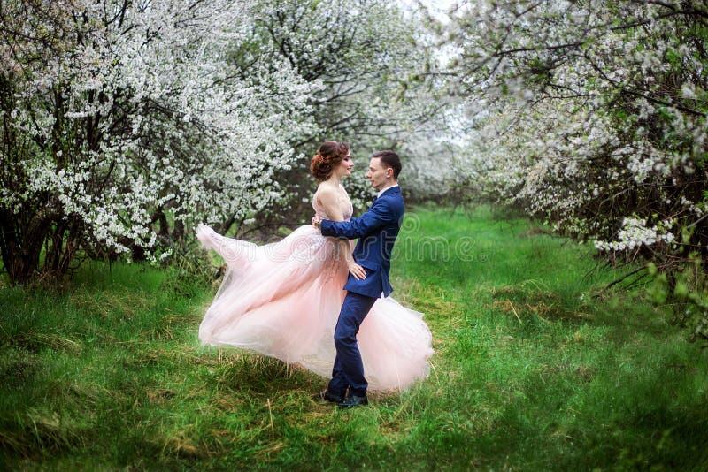 De bruid en de bruidegom in huwelijk kleden zich tegen de achtergrond van bloeiende tuinen royalty-vrije stock foto's