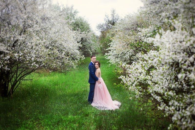 De bruid en de bruidegom in huwelijk kleden zich tegen de achtergrond van bloeiende tuinen royalty-vrije stock afbeeldingen