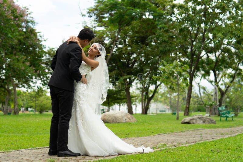 De bruid en de bruidegom koesteren elkaar voor altijd met liefde, parenhuwelijk stock fotografie