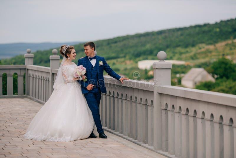 De bruid en de bruidegom lopen langs het het bekijken platform, het lachen en het glimlachen bij elkaar en hun delen royalty-vrije stock foto