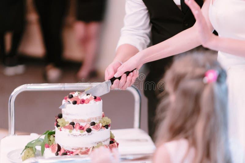 De bruid en de bruidegom snijden dichte omhooggaand van de huwelijkscake royalty-vrije stock foto's