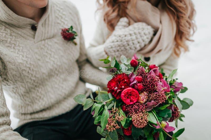 De bruid en de bruidegom in warme de winterkleren houden in handen een rustiek huwelijksboeket met rode en karmozijnrode bloemen  stock fotografie