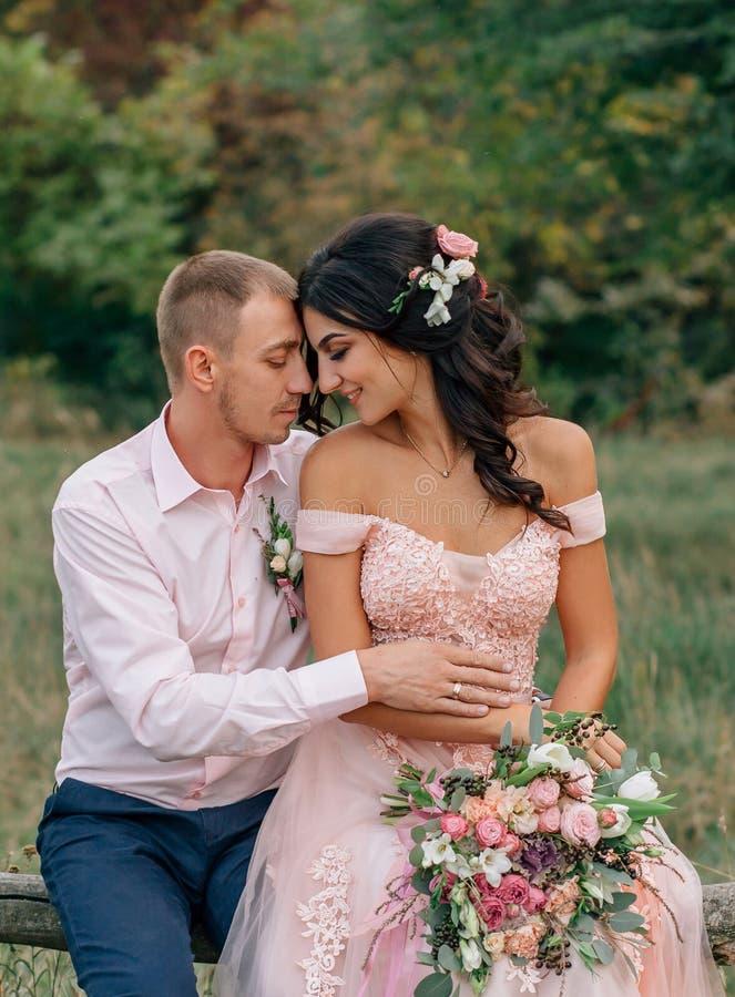 De bruid en de bruidegom zitten op een houten omheining De kerel en het meisje koesteren zacht elkaar Huwelijk in roze royalty-vrije stock foto