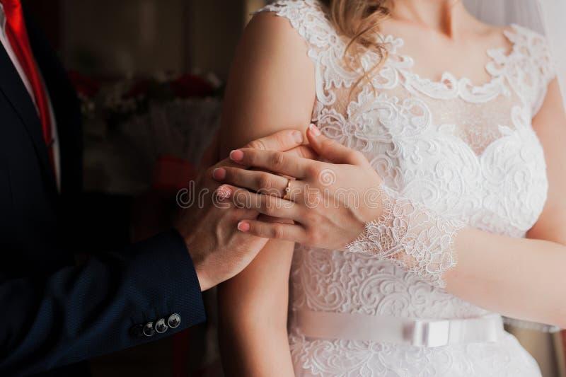 De bruid en bruidegomholdingshanden stock afbeeldingen