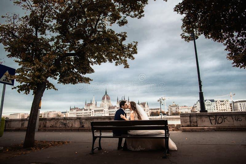 De bruid en bruidegomzitting op de bank dichtbij de rivier in de oude stad Het wieden in Boedapest stock fotografie