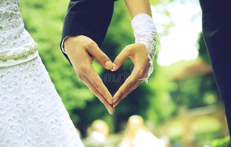 De bruid en de bruidegom dienen de vorm van hart in royalty-vrije stock afbeelding