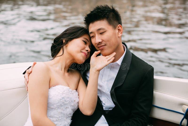 De bruid en de bruidegom drijven op een boot royalty-vrije stock foto's