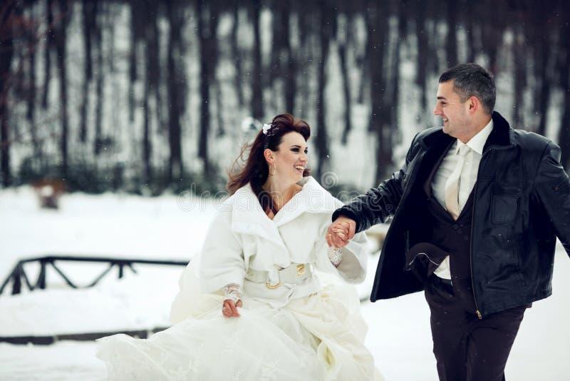 De bruid en de bruidegom hebben pret die over een park in de sneeuw lopen weath royalty-vrije stock foto's