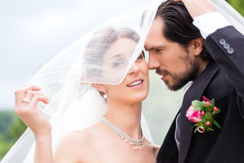 De bruid en de bruidegom het verbergen van het huwelijkspaar onder sluier stock foto